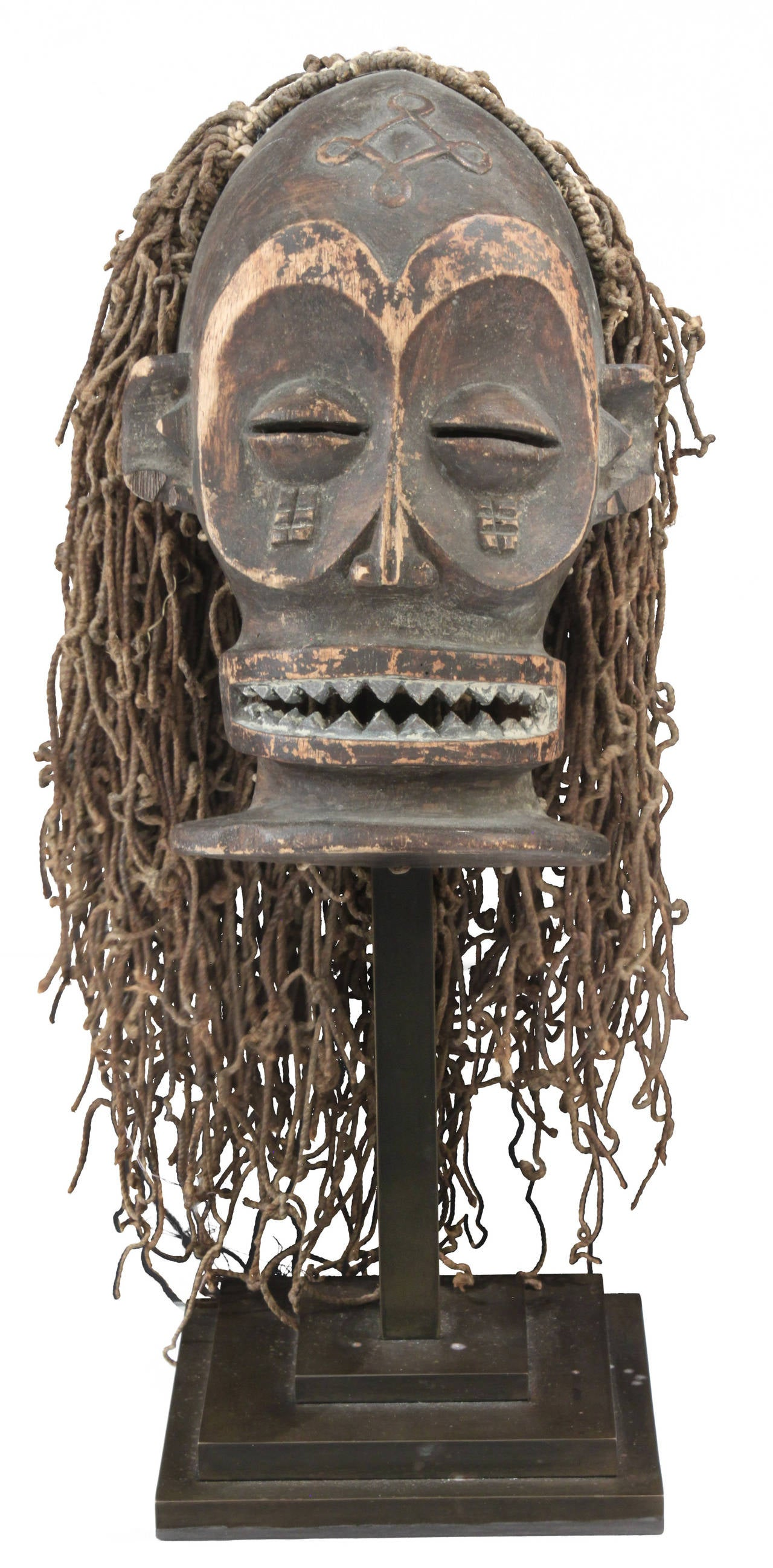 Hand-carved African male mask in the style of the Chokwe tribe of Angola on a bronze base by Karl Springer, American, 1980s (photo of original label included). Karl Springer had a scout who traveled the world seeking out exceptional handcrafted