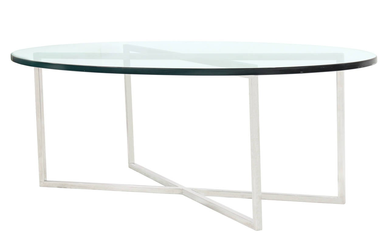 Elegant coffee table with polished steel base and oval glass top by Tommi Parzinger for Parzinger Originals, American, 1960s.