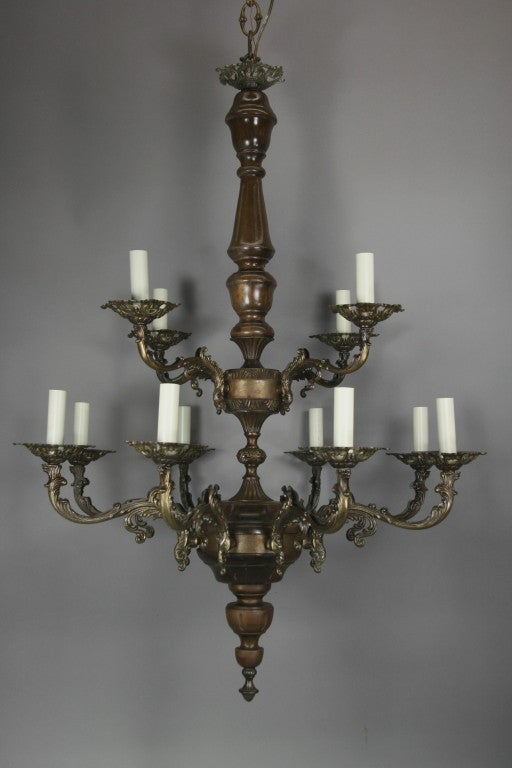 #1-2823 A two tier wood and ornate darkened brass 12-light chandelie List price $2700 now $1475 net  no additional discounts