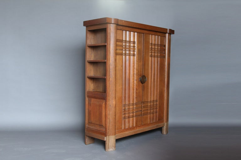 Fine French Art Deco solid oak armoire by Charles Dudouyt with sides bookcase and carved doors.