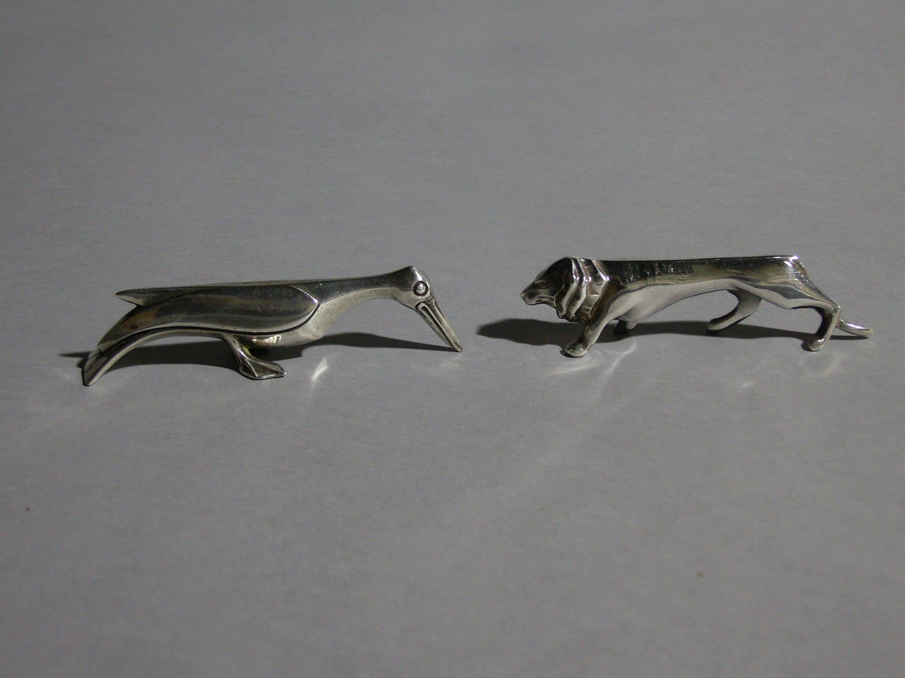 Set of 12 fine French Art Deco silver plated knife rests designed by Sandoz for the Gallia line of Christofle. All 12 animals are different. Original case.  Average size of knife rests: H 0.8 inch x L 4.3 inch x W 0.8 inch.  H 2 cm. x L 10.5 cm. x
