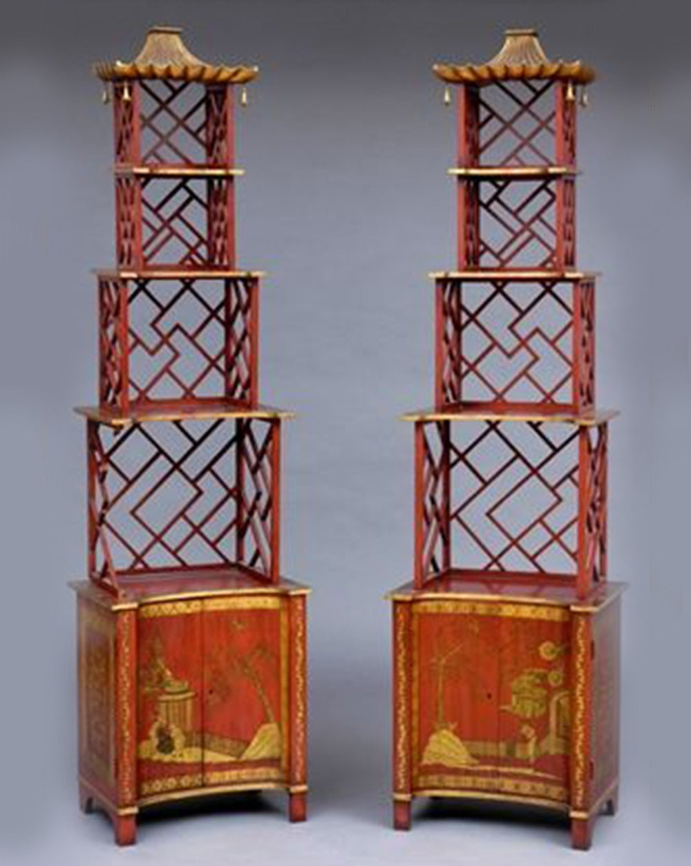 Pair of red japanned étagères in the Chinese Chippendale style. The gilt pagoda cresting is hung with bells above four graduated tiers held by open lattice and Greek key fret above a pair of concave doors painted and gilt with chinoiserie, 