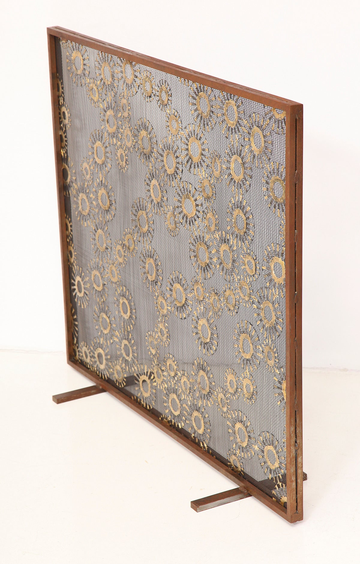 """Marie Suri  The constellation fire screen  Fire screen with scattered 2.5"""" and 4"""" steel medallions with bronze decoration. Mesh backing makes these an excellent choice for wood-burning fireplaces.  Custom inquiries welcome. Made to order"""