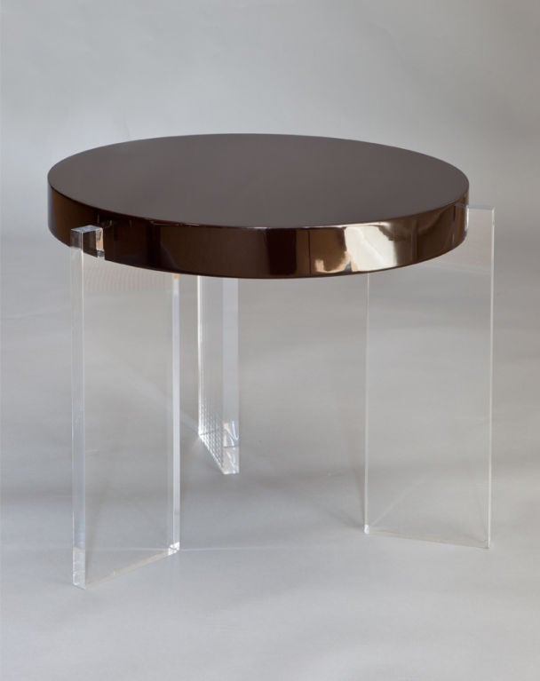 Round occasional table raised on three acrylic legs.
