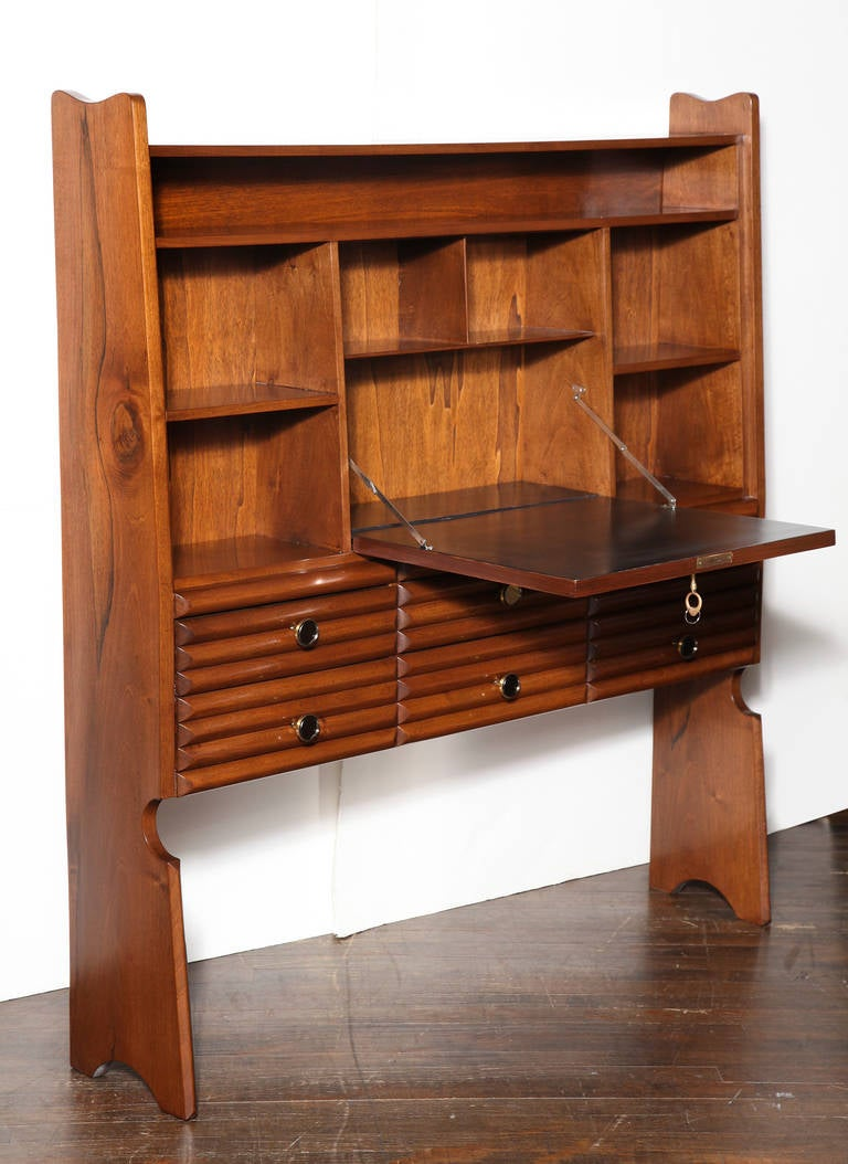 Bookcase with drop front desk by Paolo Buffa.  Petite bookcase of Italian walnut. Angular front with open storage and drop-front writing surface. Six lower drawers with wide ribbed faces and elegant circular brass pulls with mirrored fronts. An
