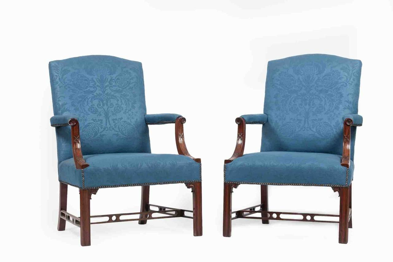 Pair of late 18th century Gainsborough armchairs. Each with an upholstered seat, shaped back, and padded open armrest. With blind fretwork on the arms, and with square legs and a pierced H-stretcher.