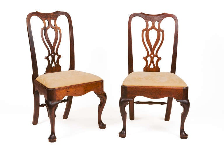 Pair of 18th century Georgian mahogany side chairs. Each with a pierced vase-shaped backs plat, cabriole legs carved with C-scrolls and pad feet and a turned stretcher between the rear legs.