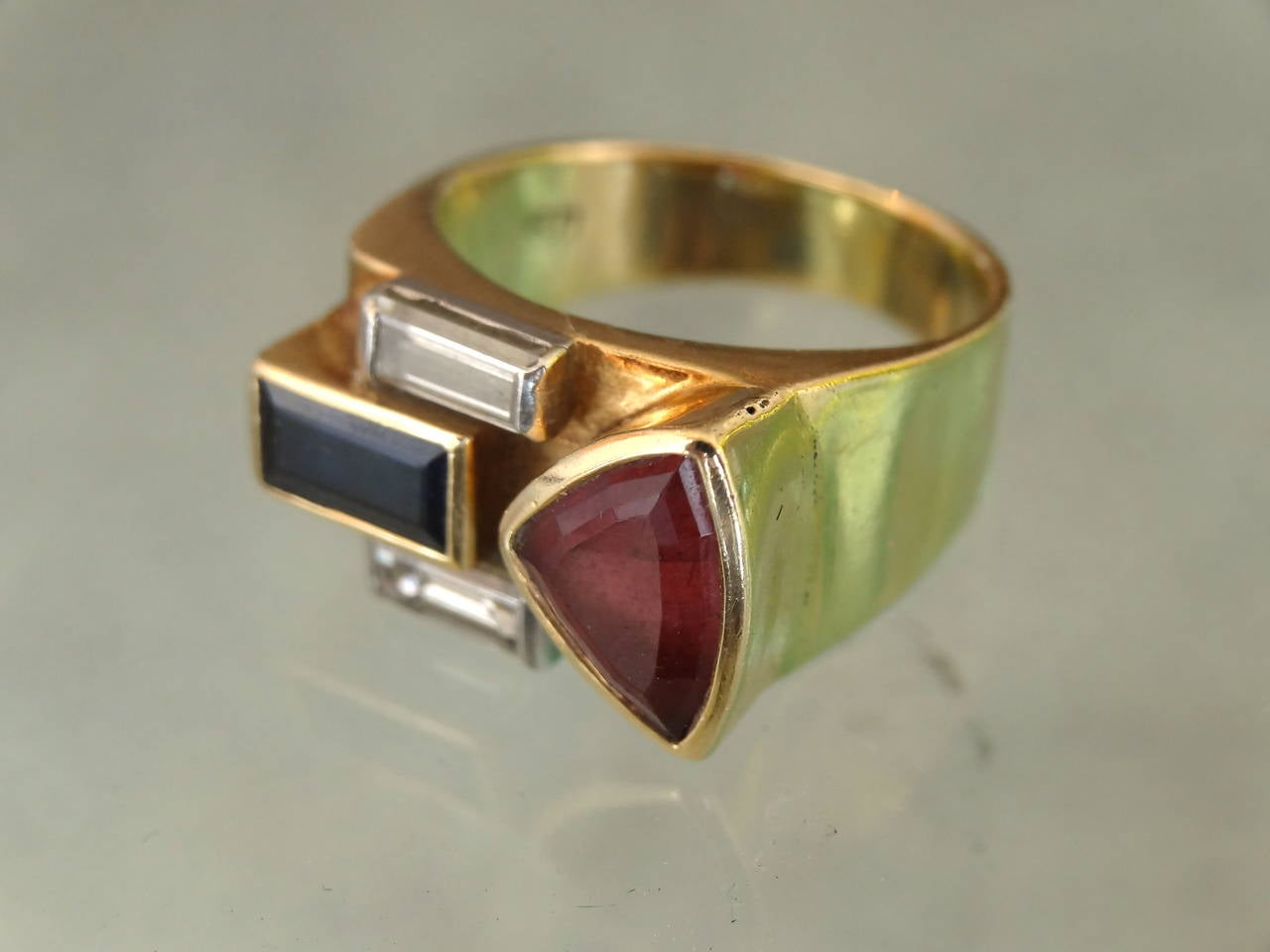 A beautifully designed ring with a multistone modern design. This ring is of 18-karat and set with stones of three colors which compliment each other. Ring has a modern Classic appeal. From 320 Central Park West Estate. I believe the stones to be