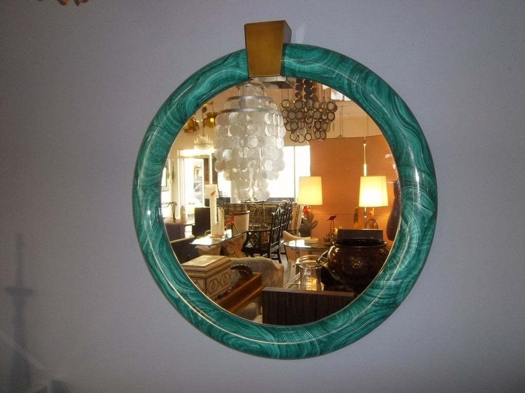A circular mirror having a deco inspiration and typical of mirrors by Karl Springer of this period. A modern and elegant mirror.