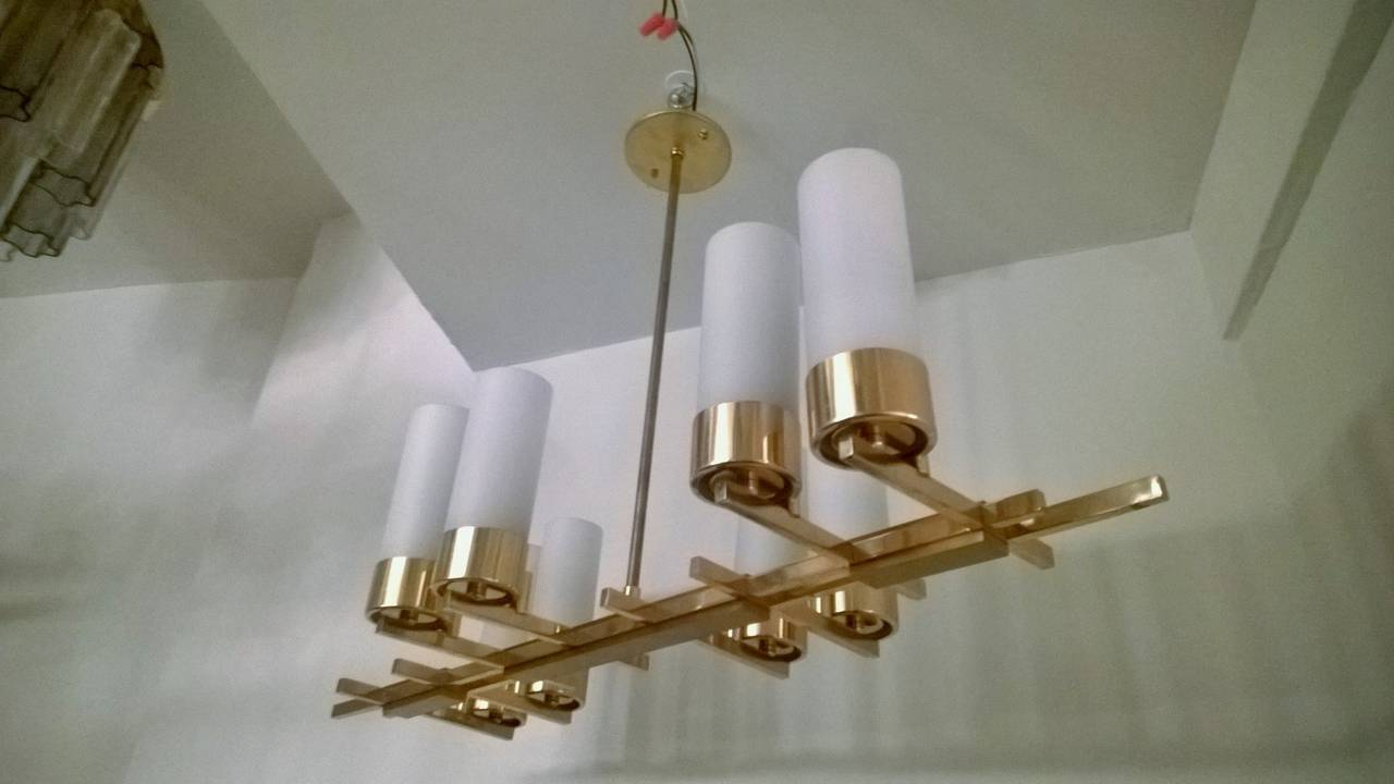 A wonderful 1960s French eight-light golden brass chandelier with white tube glass shades. Rewired.