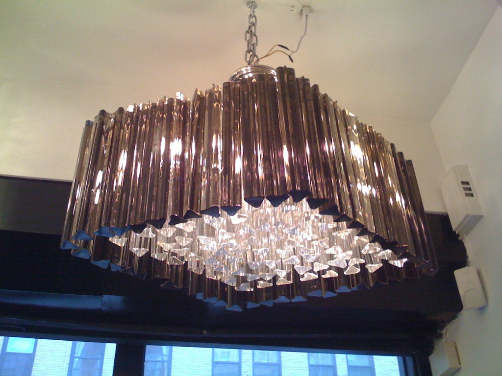 A Murano glass chandelier in a diamond shape composed of clear and smoked crystals on a chrome frame.