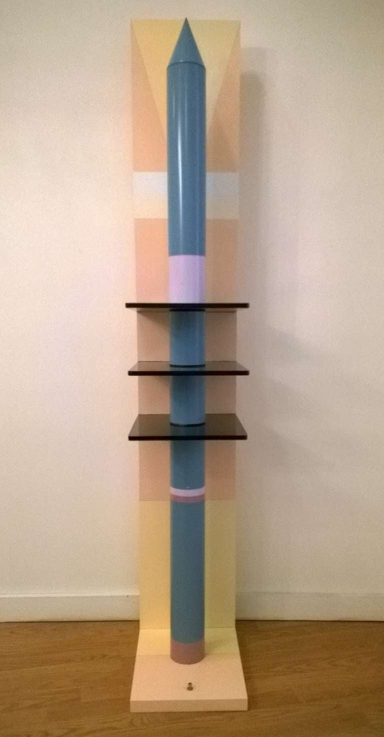 A sculptural rocket shaped floor lamp done in a purple and blue lacquered metal rocket with three smoked glass trays, a beige, pink and yellow lacquered wood base. Three shelves. Long hallogen tube.