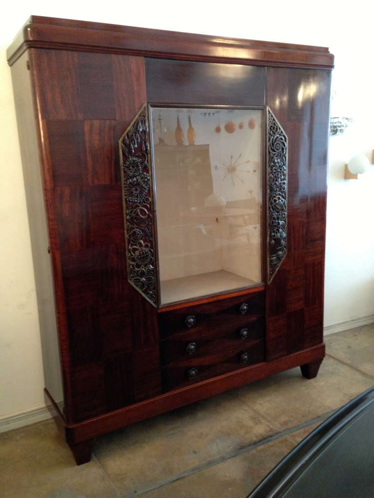 A wonderful large dark mahogany and hammered bronze French Art Deco cabinet by Louis Majorelle. It has a leaded glass door and two glass shelves. Ten interior shelves, two glass shelves, three large drawers. Signed. Provenance: Estate of Milton
