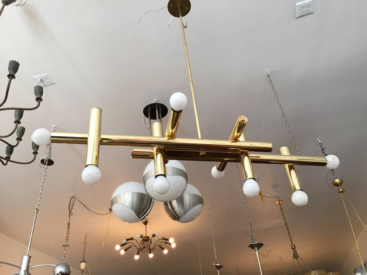 A sleek 1960s Italian Mid-Century ceiling light or chandelier composed of a high polished brass tubes fixture. Rewired. Matching flat circular disc canopy.