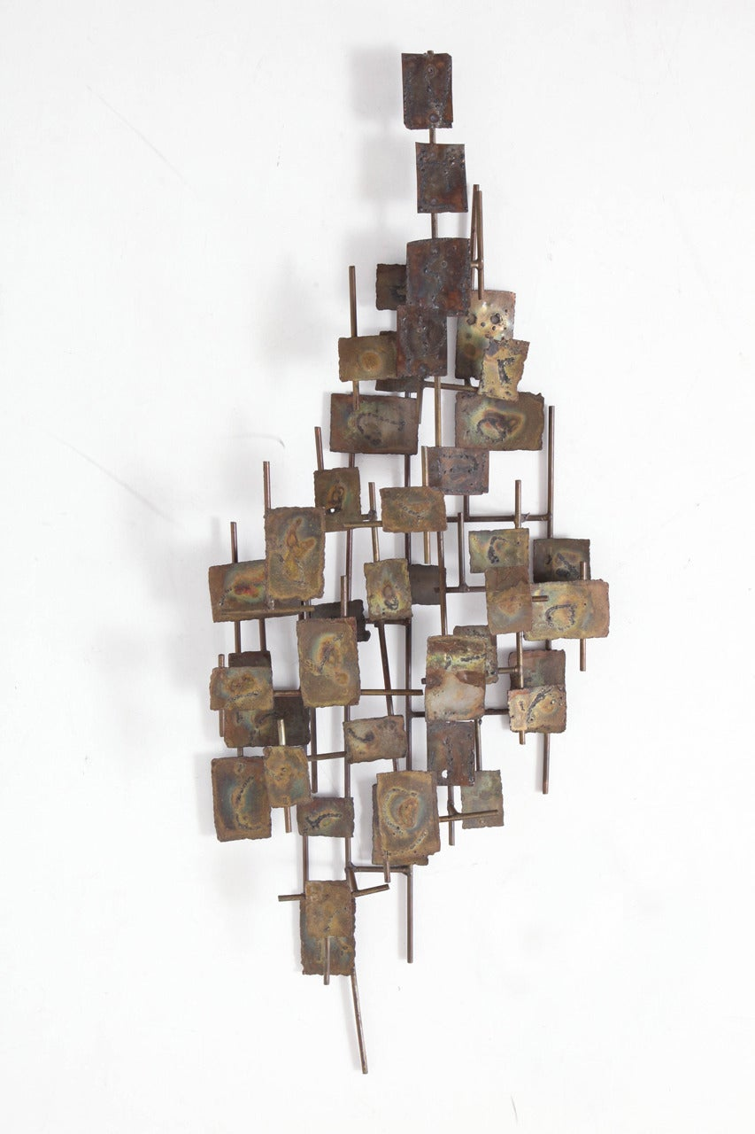 A Brutalist wall-mounted bronzed metal art sculpture by Curtis Jere.  USA. circa 1970.  Features metal rectangles in a freeform design mounted on a metal frame.  May be hung vertically (as shown) or horizontally.