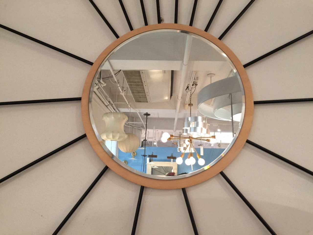 Whimsical starburst mirror.  USA, 1980s.  Blond wood frame accentuated by black dowel rays.