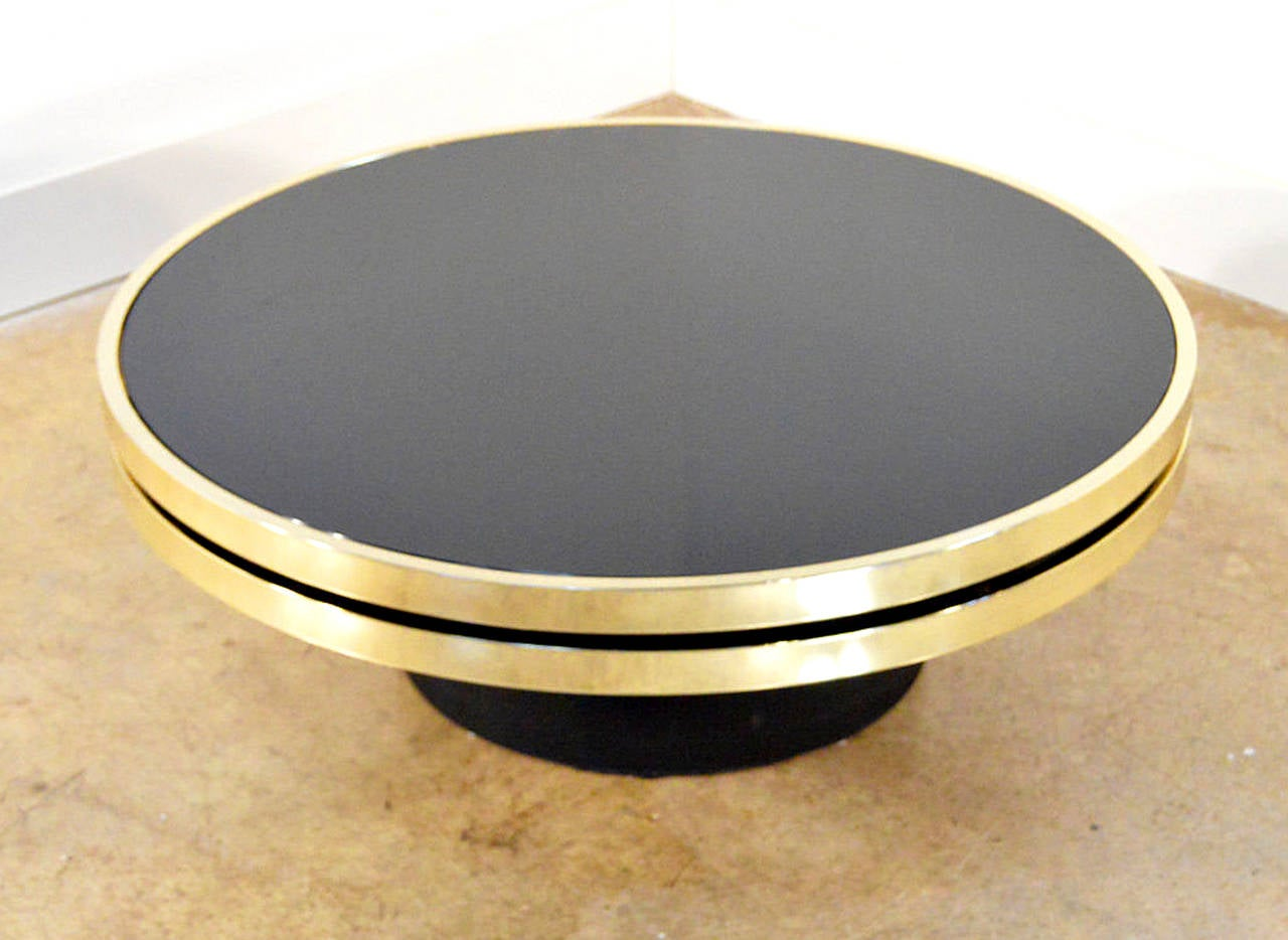 Stunning Design Institute of America brass and smoked glass swivel cocktail table with black base. USA, 1970s. Brass glistens in the light, glass is free of any chips or major scratches. Swivel mechanism works flawlessly. Table top rotates with
