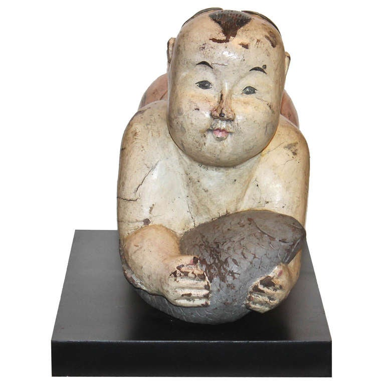 Vintage hand-carved kneeling baby bodhisattva holding a fish symbolizes blessings of abundance and prosperity. Gentle facial expression with original color lacquer makes this wood carving a treasure to be displayed anywhere in the house.