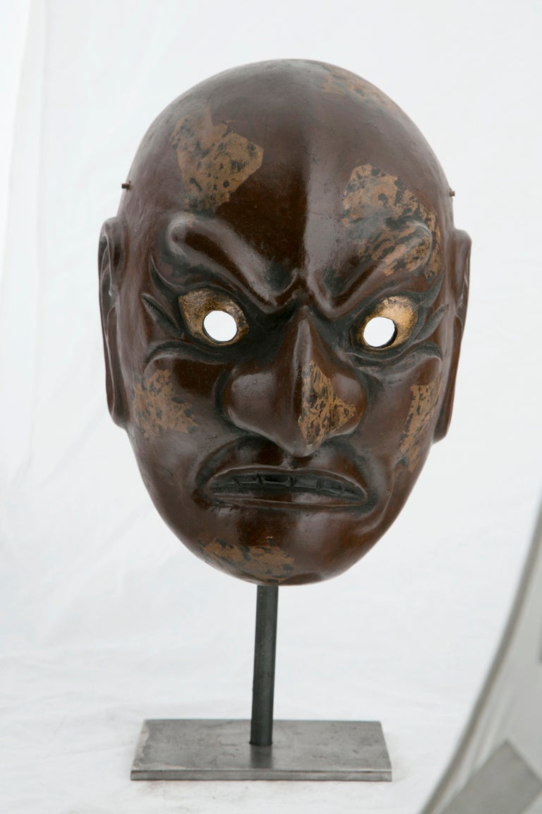 A  decorative antique lacquered gilt and painted papier mache' Noh mask made in Japan early in the 20th Century.  Performers would wear these masks while participating in traditional Japanese entertainment that bares some slight similarity to