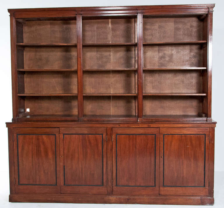 A late 19th or early 20th century English mahogany bookcase. The shelves, which are fixed, are over two cabinets with four doors probably originally a shop fixture with some alterations done by previous owner.