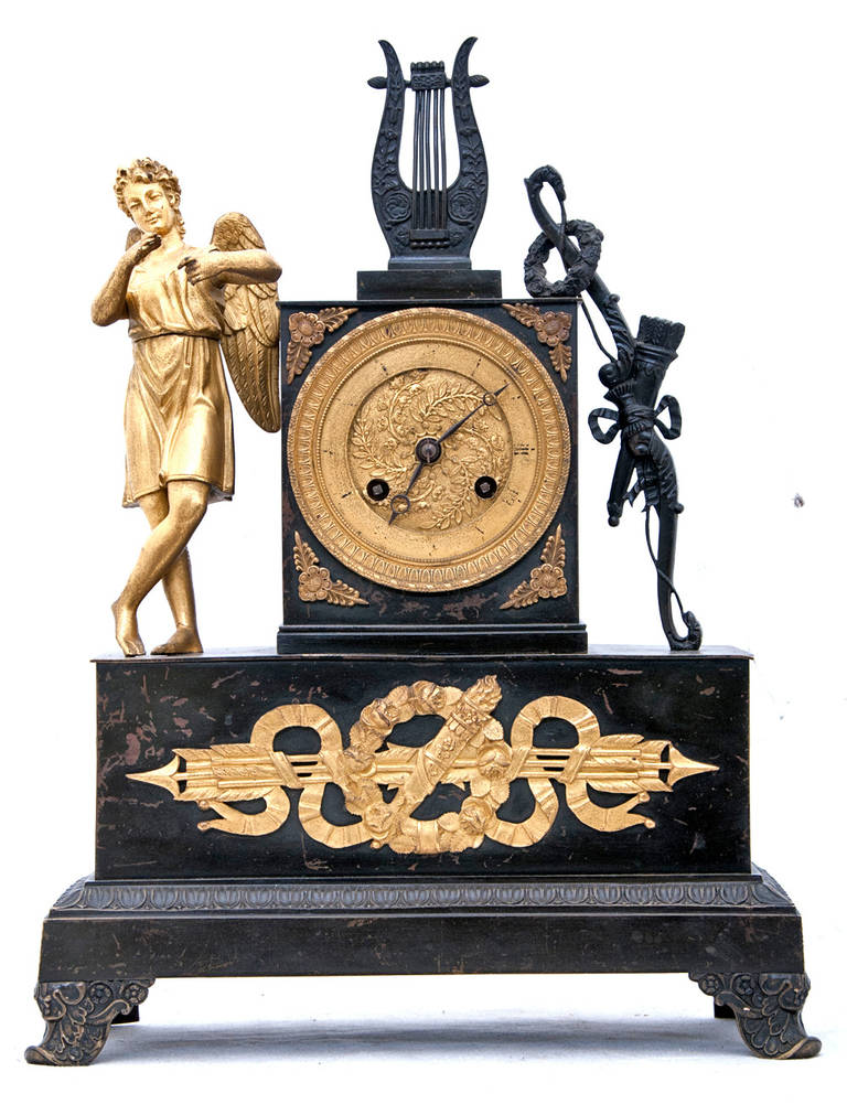 A 19th Century French Empire figural mantel clock with a gilt bronze dial. A gilt bronze winged angel or cupid is on one side with a lyre on the top and trophies on the other.  In working condition. France circa 1810
