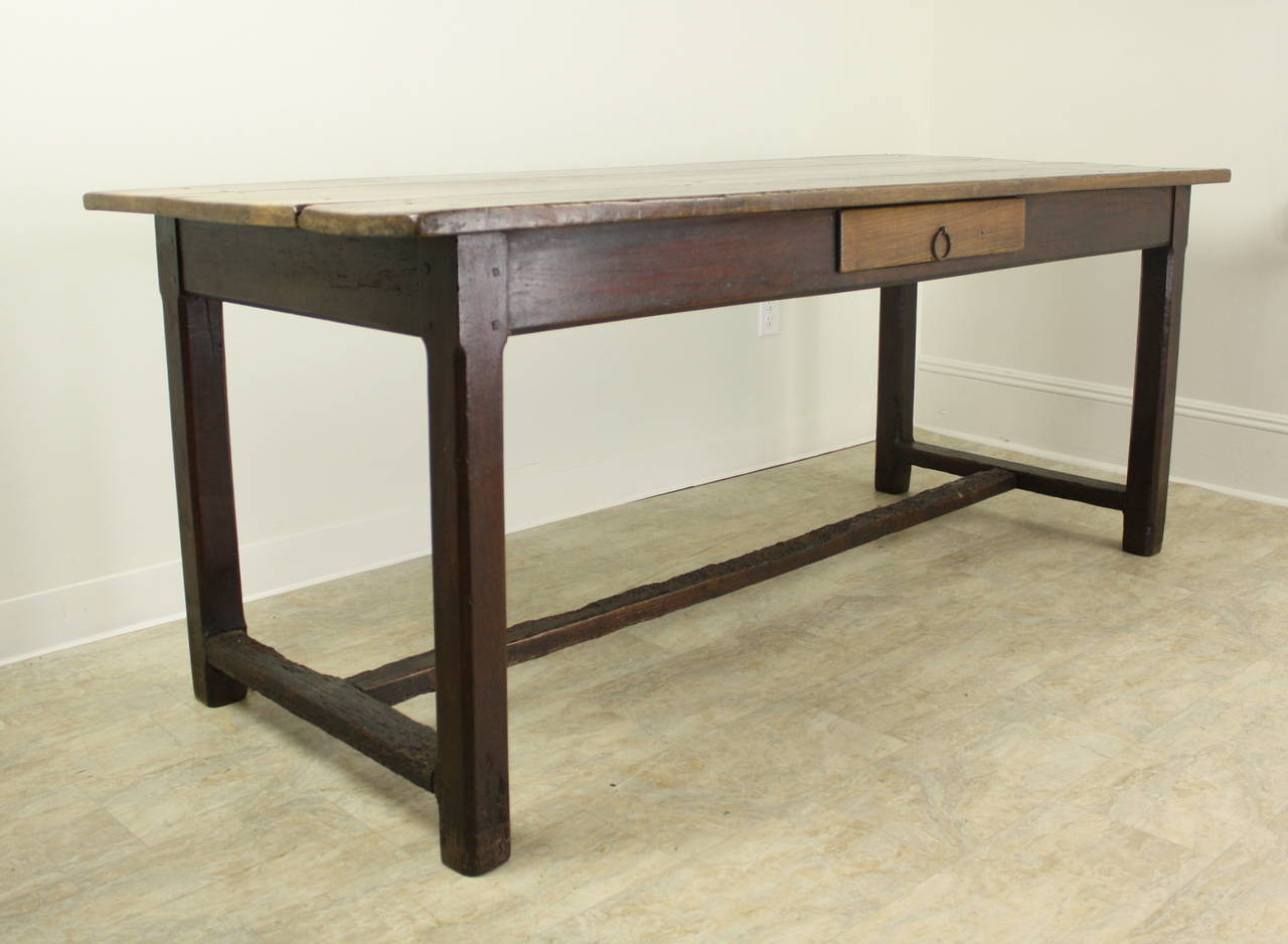 A lovely warmly colored cherry farm table with an interesting stretcher base. There are 64