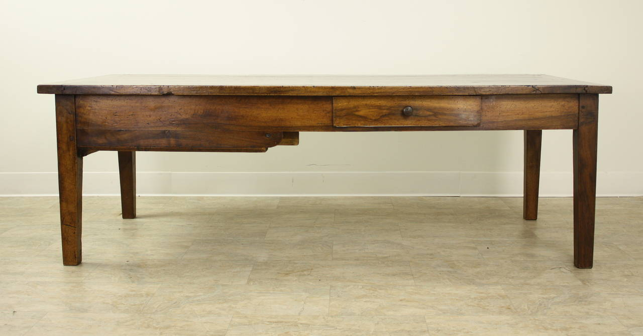 An nicely sized antique coffee table in well patinated, richly grained walnut. A small drawer on one side, as well as one deep storage drawer at the end. Interesting shaped apron and breadboard ends complete the look. A Classic!