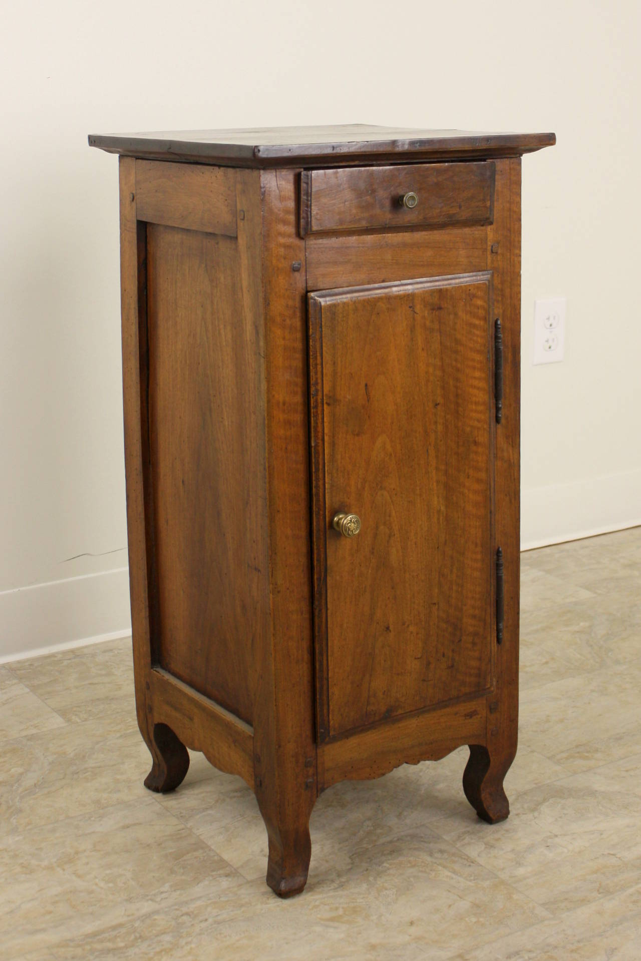 A charming antique nightstand in a very pretty walnut tone. Good storage inside, and one small drawer above.  Note the very nicely done edging around the door and drawer, and the shaped feet.  A little old damage to one of the back feet has been