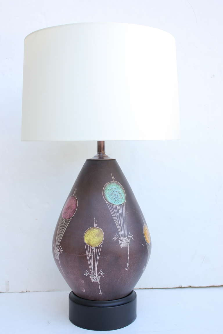 Pair of Italian ceramic lamps. Lamps depicting hot air balloons. Chocolate Ground. Lampshades are $375 additional for each. New silk wiring. Refinished bases. Double Cluster.