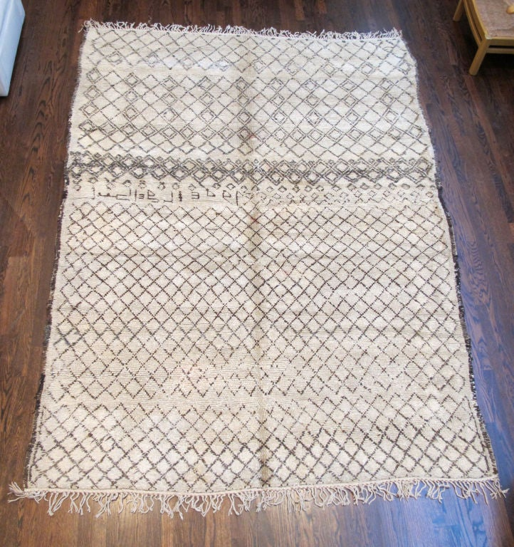 Description: Hand-loomed, pile wool rug with a natural deep ivory wool field and bold, geometric pattern in warm dark brown, fringed at both ends. Others available.