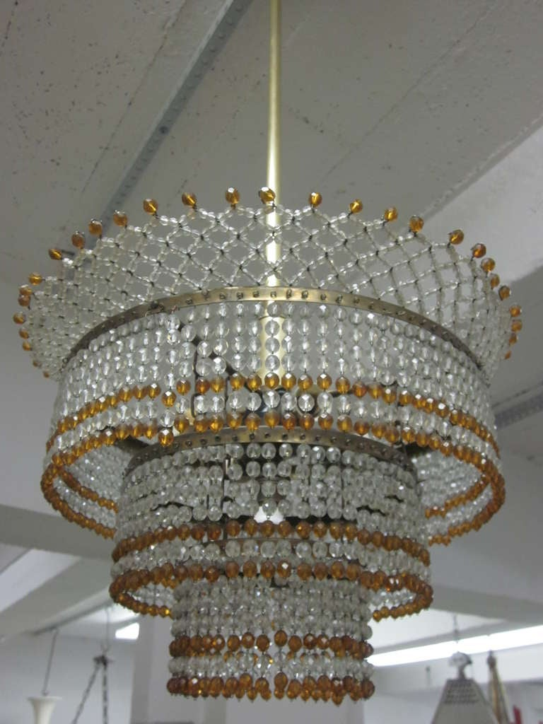 Elegant and delicate Italian Mid-Century beaded glass pendant or flush mount fixture in clear and amber Murano glass in the modern neoclassical taste. Three concentric layers of beads, four candelabra sockets. 