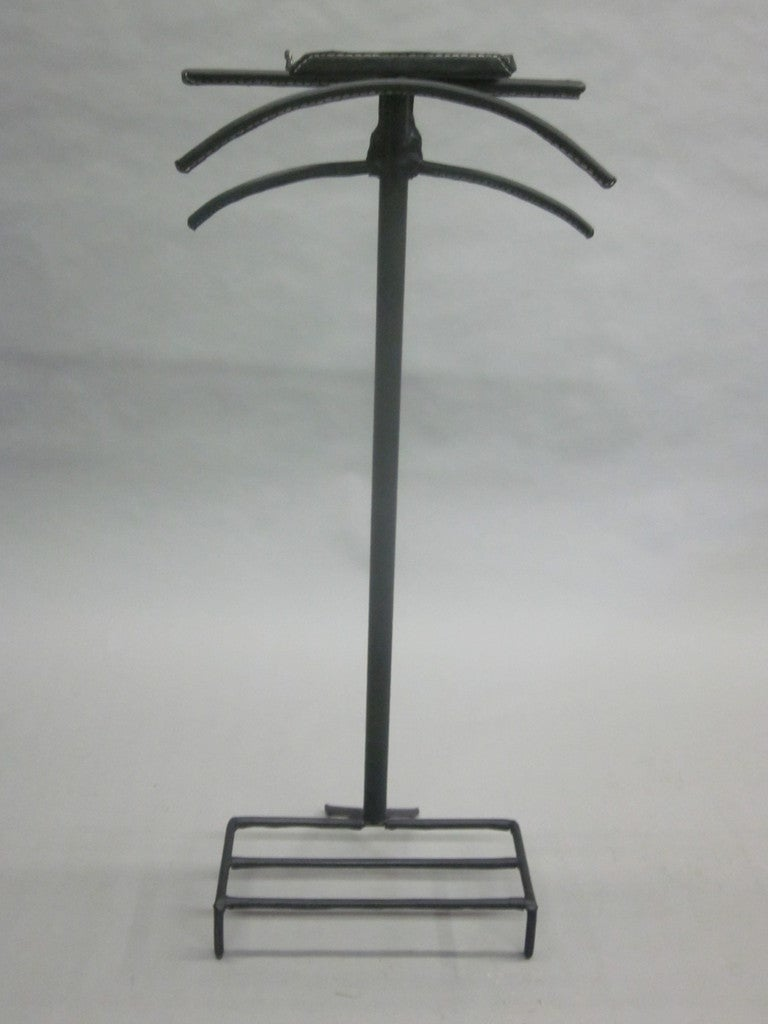 Chic, sober and luxurious French Mid-Century personal valet / coat stand by Jacques Adnet in the modern neoclassical spirit refinished in hand-stitched black leather.   The piece contains a shoe stand, coat, shirt and pants stands along with a