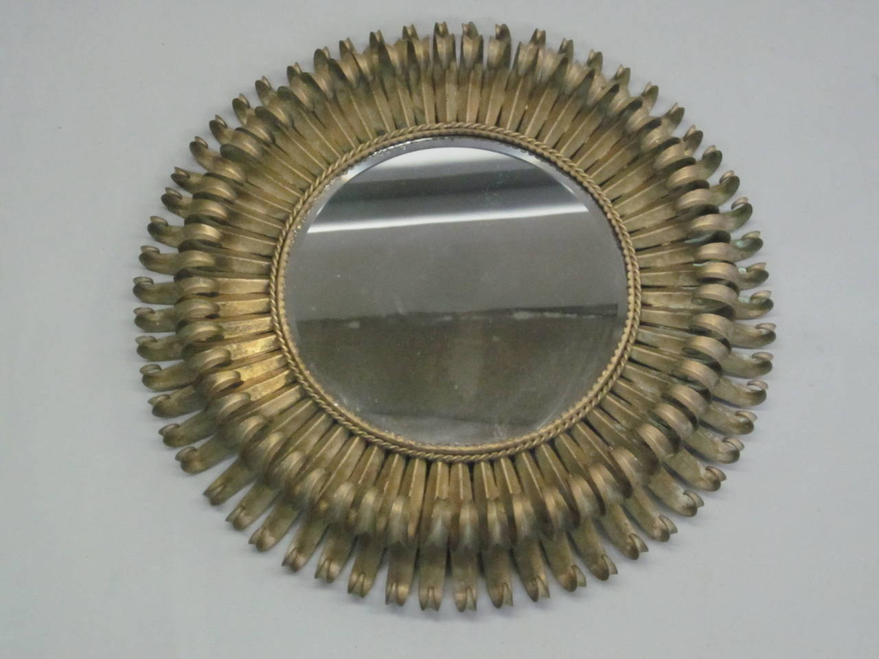 Elegant, stunning French Mid-Century mirror with a double level of sunburst rays that add depth and drama to the piece. The modern neoclassical frame of the mirror is in gilt iron.