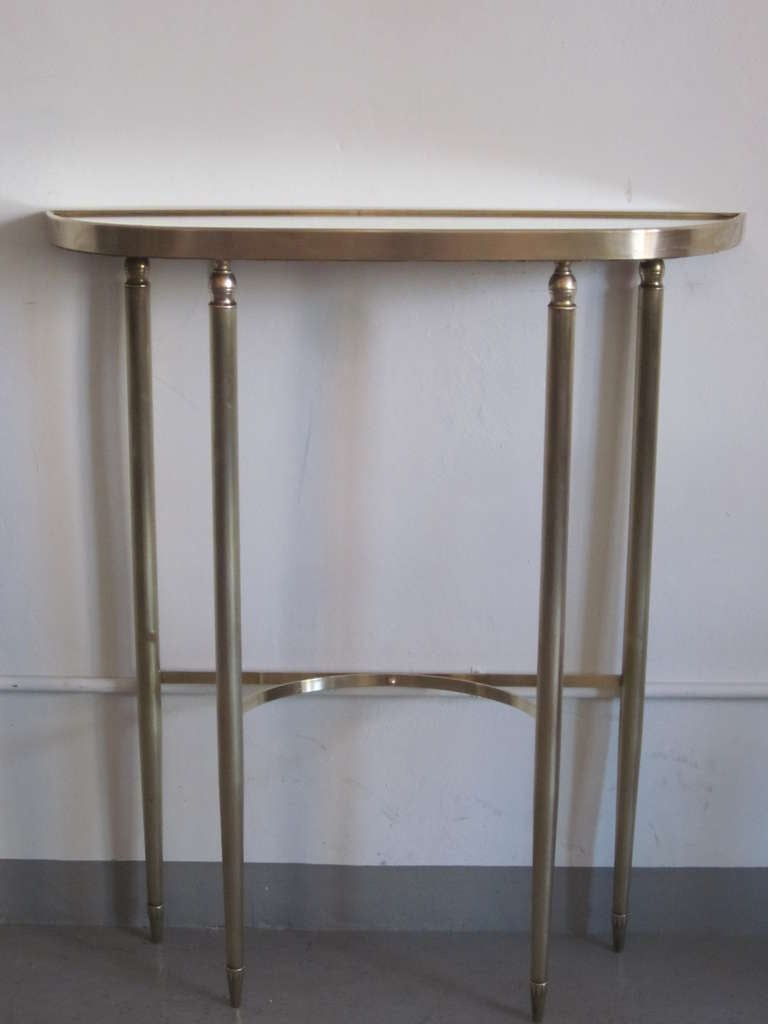 Superb modern neoclassical brass console or sofa table by Guglielmo Ulrich with an inset mirrored top resting on four tapered and fluted legs ending in exquisitely crafted sabots and braced with a bowed stretcher. 
