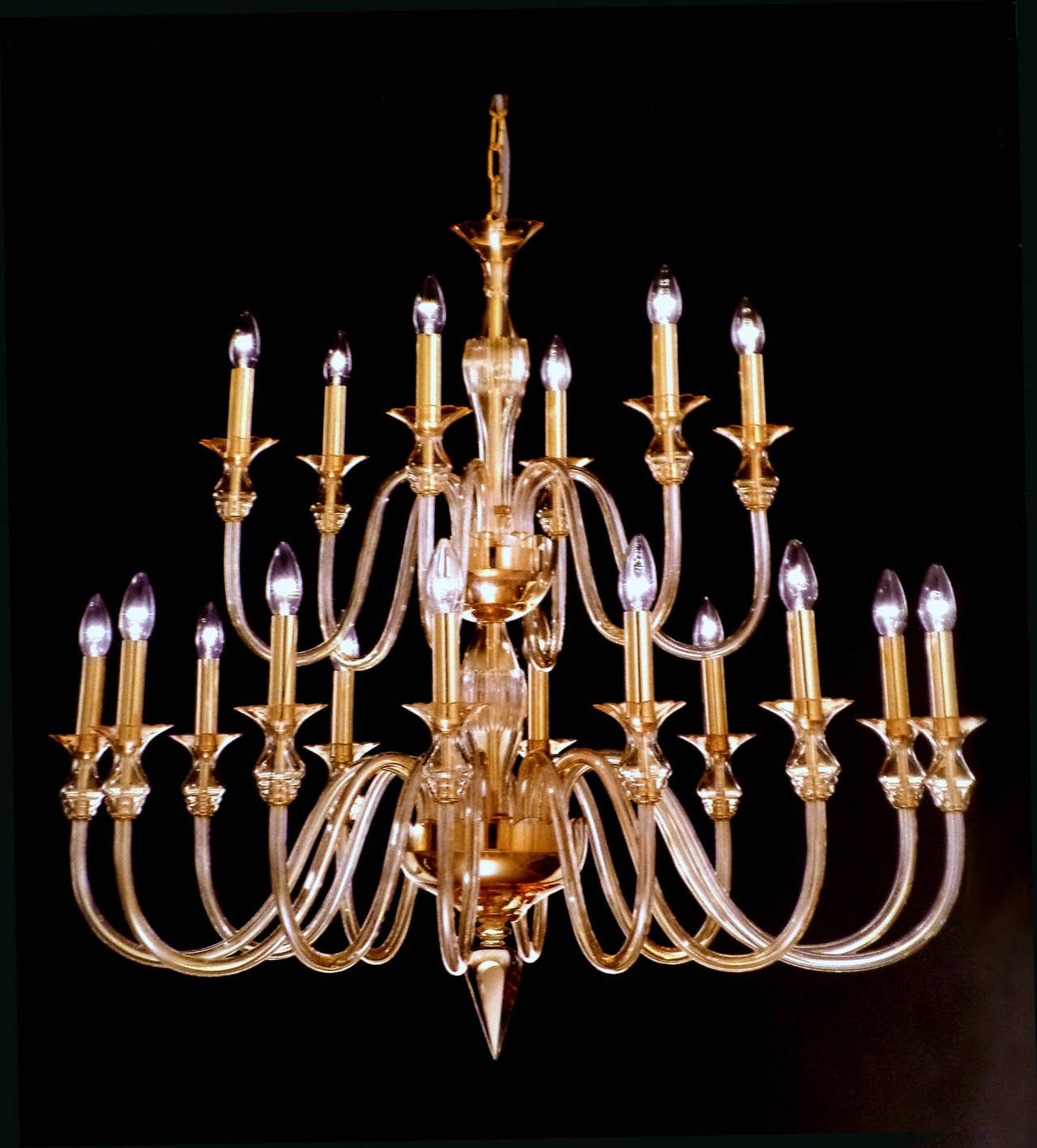 Elegant, sober double-level Venetian glass chandelier or pendant in the modern neoclassical tradition composed of twelve lower arms and six upper arms and made of amber glass with brass internal parts.