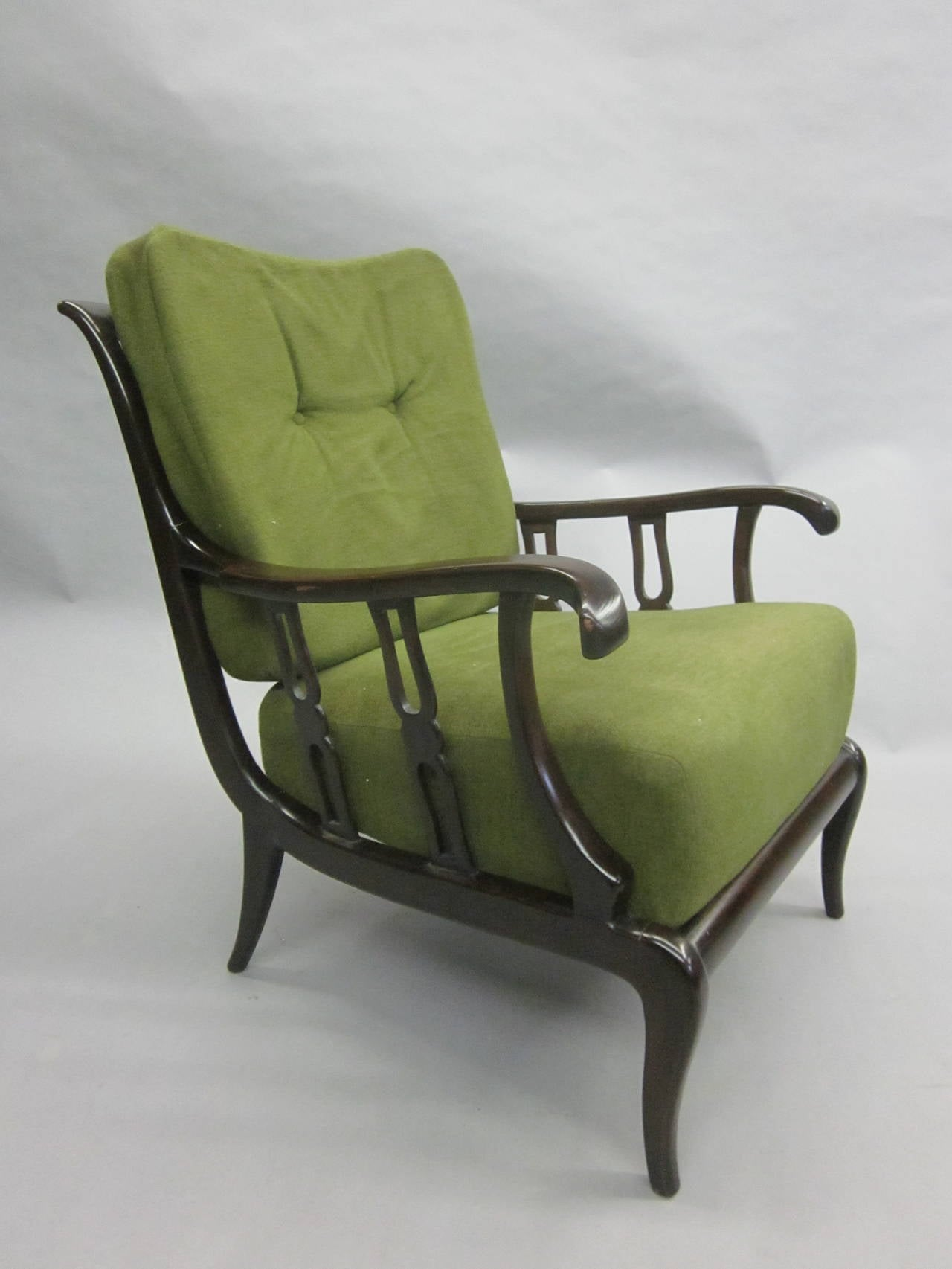 An exceptional pair of Italian 1940s lounge chairs / armchairs / club chairs by Paolo Buffa that expresses the poetry of his work featuring pure modern neoclassical frames, splayed armrests, saber legs and singular carved arm and back