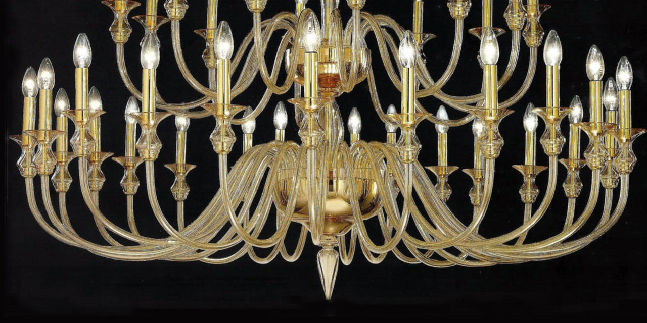 Two large, sober, elegant double tier Venetian glass chandeliers in clear amber glass with 24 lower arms and 12 upper arms and set up for 36 candelabra lights at up to 60 watts each. A pure, modern neoclassical statement.   The height of the