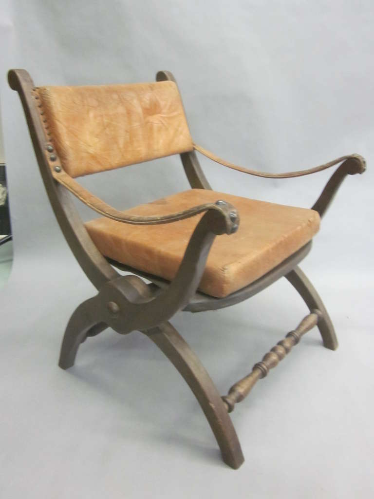 Pair of Italian Mid-Century Modern neoclassical lounge chairs or club chairs featuring a Classic X-form or Curile form frame structure with leather seats and backrests.