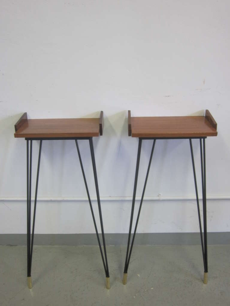 Sexy pair of French Mid-Century wall consoles or nightstands with sober, clean, modern lines attributed to Pierre Guariche. The pieces are composed of sleek wrought iron legs ending in brass sabots and support hardwood tops. They are