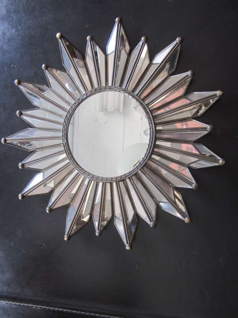 Elegant French Mid-Century sunburst wall mirror uniting modern and neoclassical sensibilities with delicate fully mirrored sunburst rays, each cut on angles and held within a copper and brass frame. Central plate is also mirror.  A small gem.