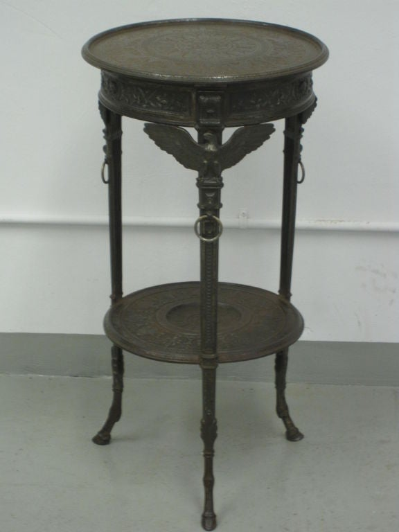 Rare Napoleon III end / side tables in cast iron reflecting a modern roman sensibility with dramatic details including incised tops, applied eagles, ring pulls and hoofed feet.