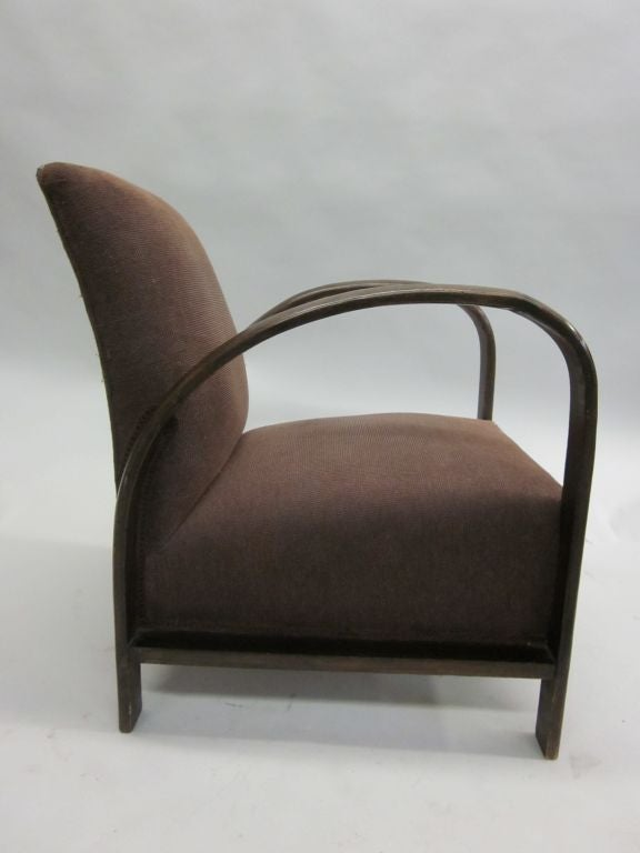 Elegant pair of French lounge chairs/club chairs/armchairs in the manner of Jacques Adnet showing the influence of early modernism and Art Deco with it clean, sober lines and streamlined form.  Literature: A similar model is published in