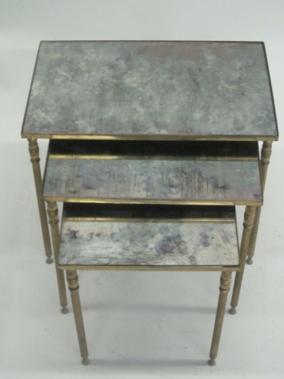 Elegant ensemble of three French Mid-Century solid brass nesting tables / side tables in the Modern Neoclassical spirit each with mirrored tops. Dimensions of top table are approximately: H 18 x 18 x 11.5.  Tops shown are for demonstration only.