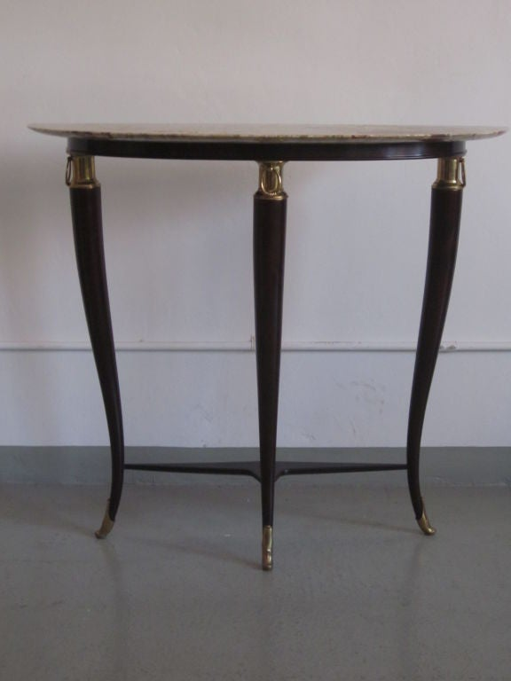 An elegant post Art Deco or modern neoclassical console by Paolo Buffa with stunning hand carved wood legs in a stunning curved form and united by an angular 3 part stretcher, finished with brass ring pull decorations and the feet end in gilt bronze