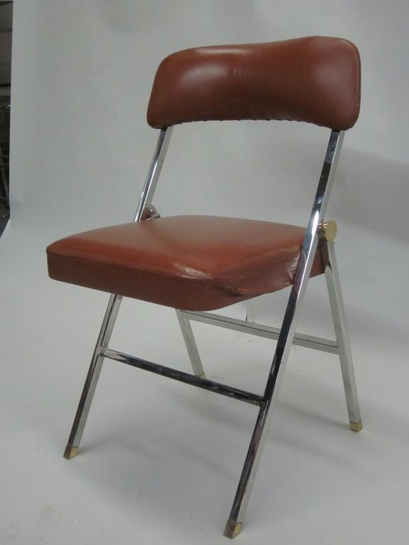 Ten French Mid-Century Modern leather folding chairs for dining in a sleek modern form including chic saber legs; luxuriously appointed in nickel with angled brass sabots and brass hardware detailing.
