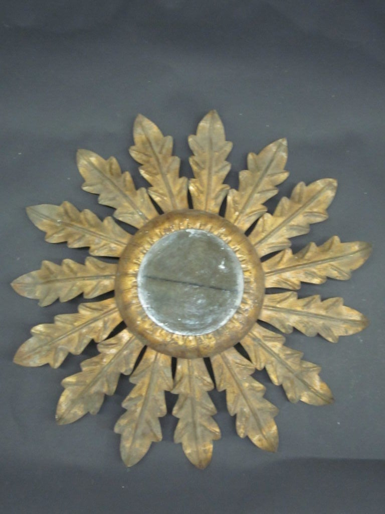 French Mid-Century gilt iron wall mirror utilizing a leaf motif to form the the image of a sunburst.