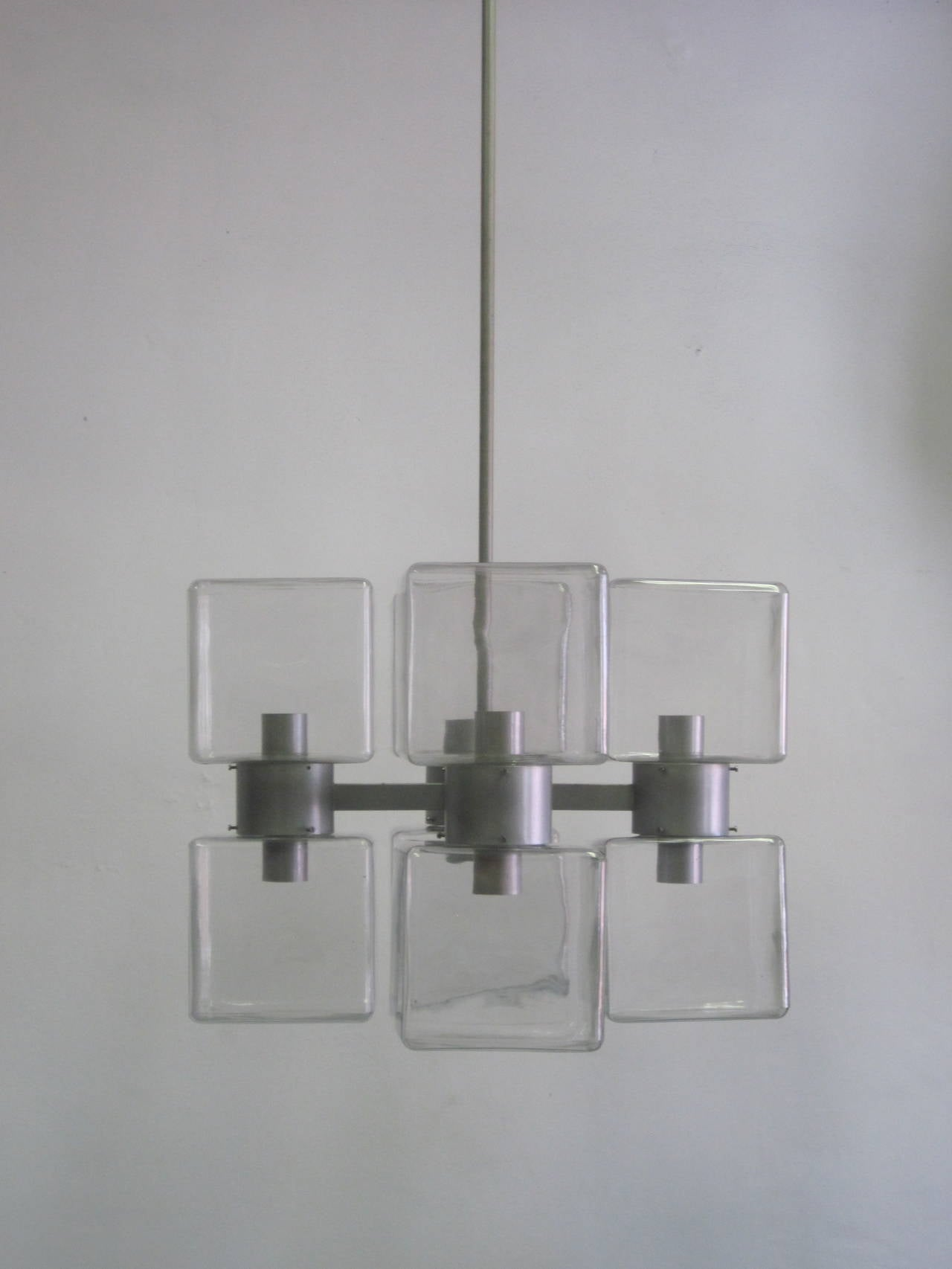 Elegant, sober and pure Italian Mid-Century Modern chandelier composed of eight mold blown clear Murano glass reflectors arranged in a cross pattern. The glass can oriented to form a square or angular pattern by adjusting the angle of the