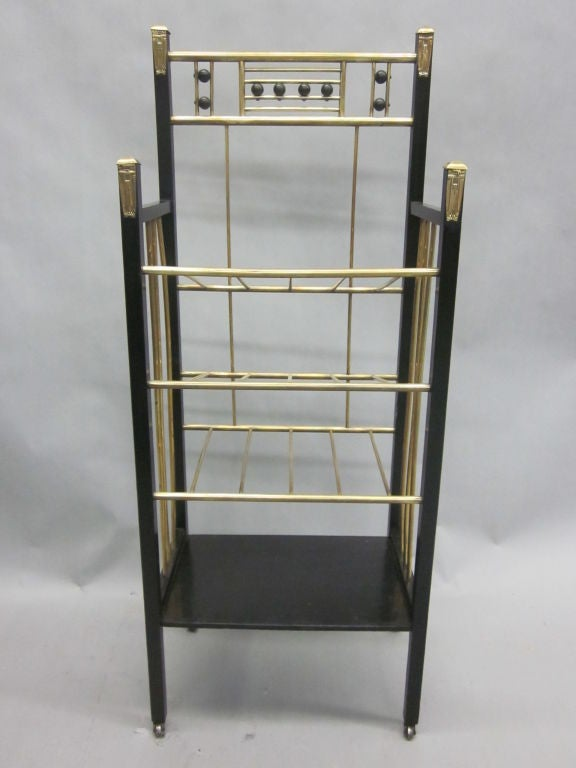 An exquisite early 20th century ebonized wood etagere / magazine stand / bookcase that suits any contemporary or traditional environment.