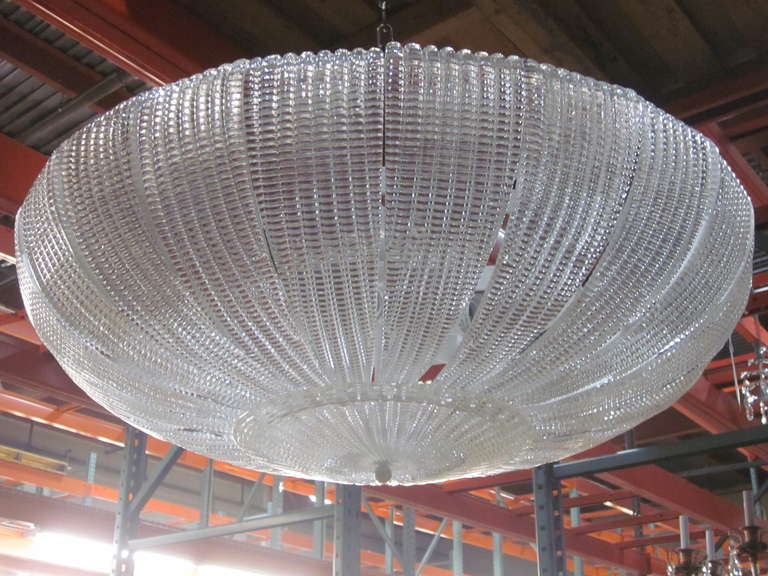 A large, elegant Italian Venetian glass chandelier or pendant in the style of Carlo Scarpa for Venini in a stunning domed form and in a sober, thick, clear mold blown glass pattern reminiscent of the modern neoclassical period of the 1930s. The