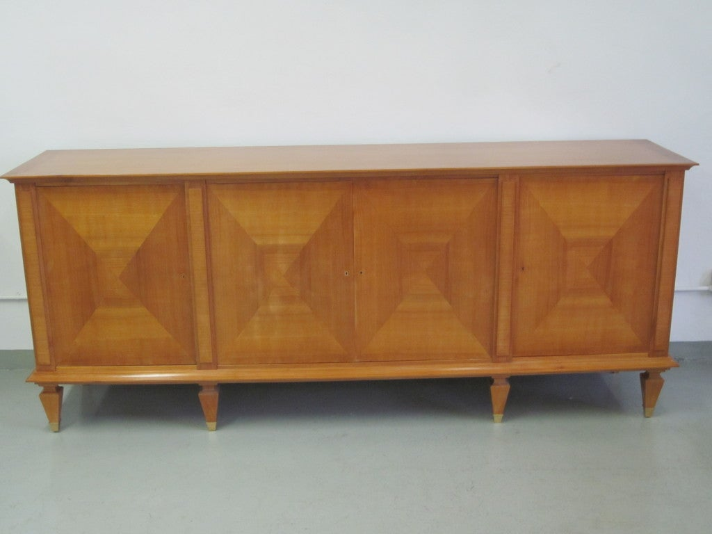 Rare sideboard / buffet by André Arbus reflecting the exalted modern neoclassical vocabulary of France's master of architecture and interiors of the 1940s. The stunning post art-deco cabinet sits on six legs each terminating in tapered legs covered